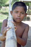 Portrait Indian boy trudging with bamboo pole Stock Photography