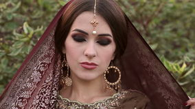 Portrait of Indian bride with covered head in park stock video