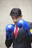 Portrait of an Indian businessman wearing blue boxing gloves against gray background Stock Photo