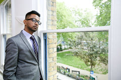 Portrait of Indian Businessman wearing glasses standing by the window Royalty Free Stock Photos