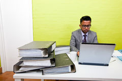 Portrait of Indian Businessman working on his laptop computer at his desk Stock Photography