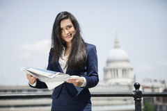 Portrait of Indian businesswoman holding newspaper with St. Paul's Cathedral in background Royalty Free Stock Photography
