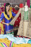 Portrait of Indian designer measuring traditional outfit at design studio Stock Photography