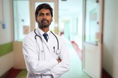 Portrait of indian doctor. Portrait of male indian doctor with serious expression and crossed arms wearing white coat having open door on cliniorridor as royalty free stock photography