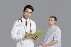 Portrait of Indian doctor writing on clipboard with patient sitting besides Royalty Free Stock Image
