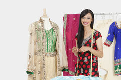 Portrait of Indian female dressmaker standing by a dummy dressed in traditional wear Royalty Free Stock Image