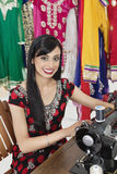 Portrait of an Indian female dressmaker using sewing machine stock photography