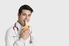 Portrait of Indian male doctor eating banana over white background Stock Photos