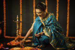 Portrait of Indian Woman celebrating Diwali festival by Lighting the lamp. Diwali is the biggest festival of India