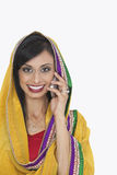 Portrait of Indian woman in traditional wear attending phone call over white background Stock Image
