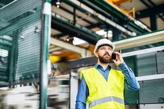 A portrait of an industrial man engineer with smartphone in a factory, working. royalty free stock image
