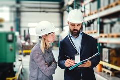 A portrait of an industrial man and woman engineer with clipboard in a factory, working. stock image