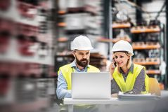 A portrait of an industrial man and woman engineer with laptop in a factory, working. stock photo
