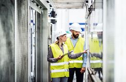 A portrait of an industrial man and woman engineer with tablet in a factory, working. royalty free stock photo