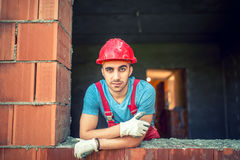Portrait of industrial worker on construction site, sitting and relaxing after a hard day at work. Brick mason worker. With protective gear Royalty Free Stock Image