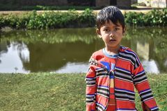 Portrait of An innocent poor boy of India standing on a ponds side and looking at camera, wearing the traditional dress. Outdoors photography stock photos