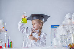 Portrait of inquisitive girl looking at test tube Royalty Free Stock Images