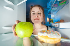 Portrait from inside the fridge of woman taking apple Royalty Free Stock Image