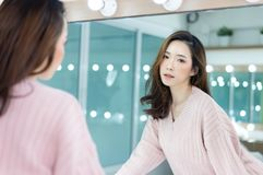 Portrait of inspired caucasian Asian lady wearing knitted sweater pink with beautiful makeup looking at camera a mirror in studio royalty free stock image