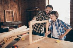 Portrait inspired child boy positive cheerful daddy craftsmen occupation workstation masterclass hardwood desktop desk. Portrait inspired child boy positive royalty free stock photo