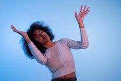 Attractive yong african american woman dancing and having fun in moody disco light royalty free stock photography