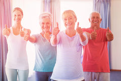 Portrait of instructor and seniors with thumbs up Stock Images