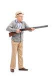 Portrait intégral d'un aîné fâché tenant un fusil Photographie stock