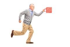 Portrait intégral d'un monsieur mûr courant avec un cadeau b Photographie stock libre de droits