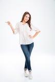 Portrait intégral d'une femme heureuse dirigeant le doigt loin Photos stock