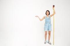 Portrait intégral d'une fille sérieusement jolie, tenant la mesure Image libre de droits