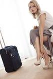 Portrait intégral de jeune femme d'affaires enlevant ses chaussures dans la chambre d'hôtel images libres de droits