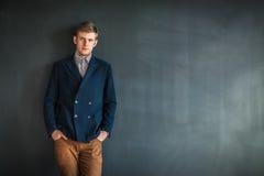 Portrait intégral de l'homme sérieux bel se tenant contre le GR Photographie stock