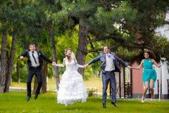 Portrait intégral des ajouter de nouveaux mariés à sauter de demoiselles d'honneur et de garçons d'honneur Image stock