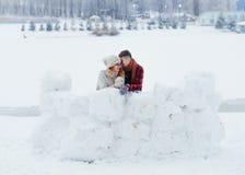 Portrait intégral sensible des couples riants gais construisant le bonhomme de neige dans le village pendant la chute de neige Photographie stock