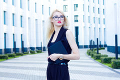 Portrait of intelligent blonde woman with a notebook on the background of the business center. Royalty Free Stock Photography