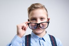 Smart schoolchild putting on spectacles royalty free stock photo
