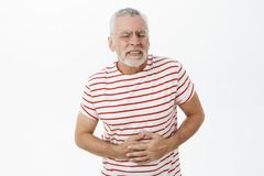 Portrait of intense bothered old man with grey beard and hair in glasses feeling pain and discomfort pressing hands to. Belly suffering from stomach ache having stock photos