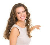 Portrait of interested young woman pointing back Stock Images