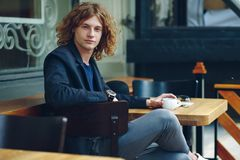 Portrait interesting reddish man posing with coffee. Portrait young fashionable interesting man with curly reddish hair, wearing jacket and vintage watch Stock Image