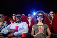 Portrait of international couple having date in cinema. Portrait of international couple having date in cinema theater. Pair sitting near, drinking sparkling stock images