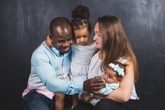Portrait of an international family with two children on a black wall background.  stock image