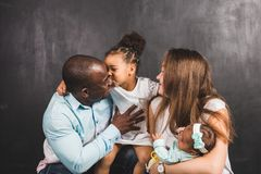 Portrait of an international family with two children on a black wall background.  stock images