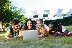 portrait of interracial young friends with laptop resting on green lawn stock photo