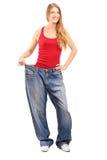 Portrait intégral d'une femelle de perte de pesage avec de vieilles paires de jea Photographie stock