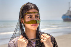 Portrait of an Iranian girl in traditional dress southern Iran. Girl in mask bandari woman, beach of Persian Gulf, Hormozgan province, southern Iran Stock Image