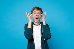 Portrait of irritated angry shocked young man in casual clothes screaming rising, spreading hands isolated on blue royalty free stock images