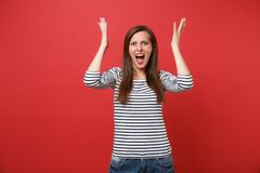Portrait of irritated angry young woman in striped clothes screaming, rising and spreading hands isolated on bright red. Wall background. People sincere royalty free stock photography