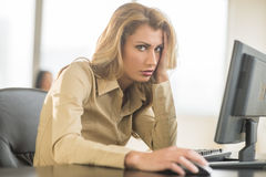 Portrait Of Irritated Businesswoman Sitting At Computer Desk Stock Images
