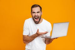 Portrait of irritated man 30s in white t-shirt screaming and holding silver laptop, isolated over yellow background. Portrait of irritated man 30s in white t royalty free stock image