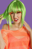 Portrait of irritated young funky woman standing over purple background Stock Photography